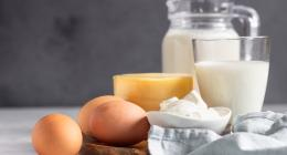 Dairy products arranged on a table: milk in a jug, cheese and eggs